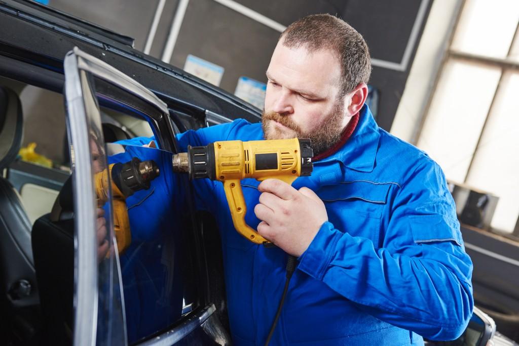 man repairing car windshield