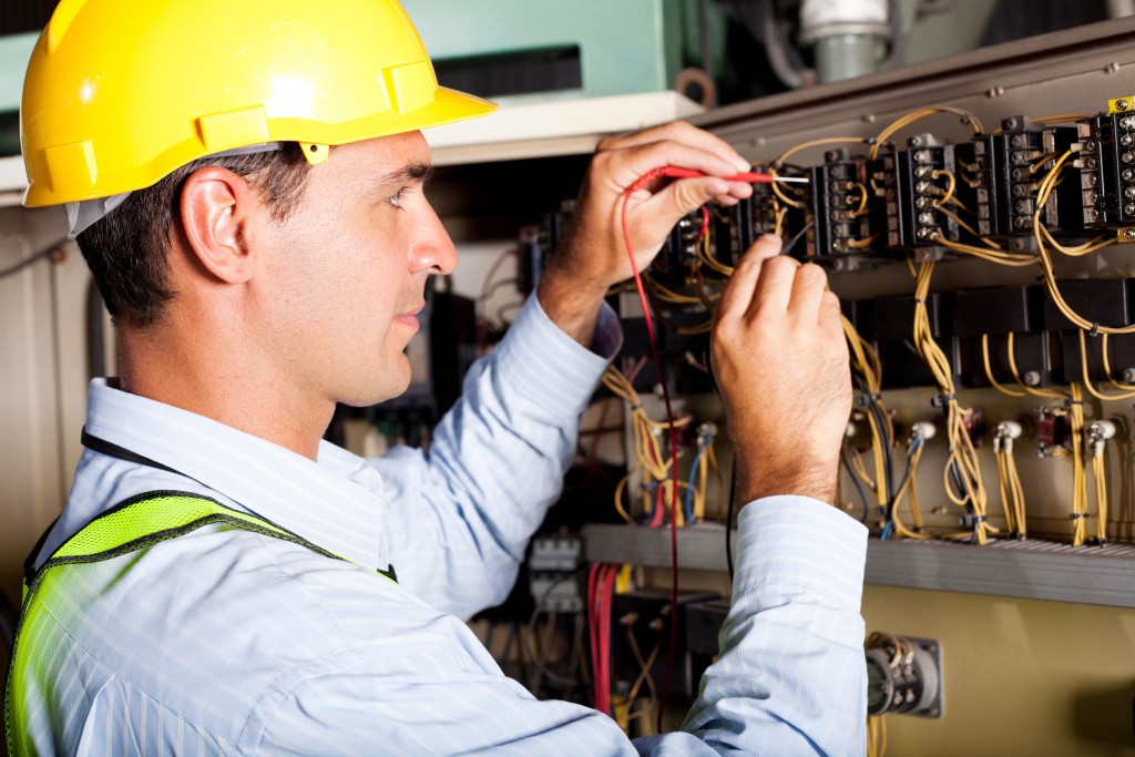 Male electrician testing electric wires
