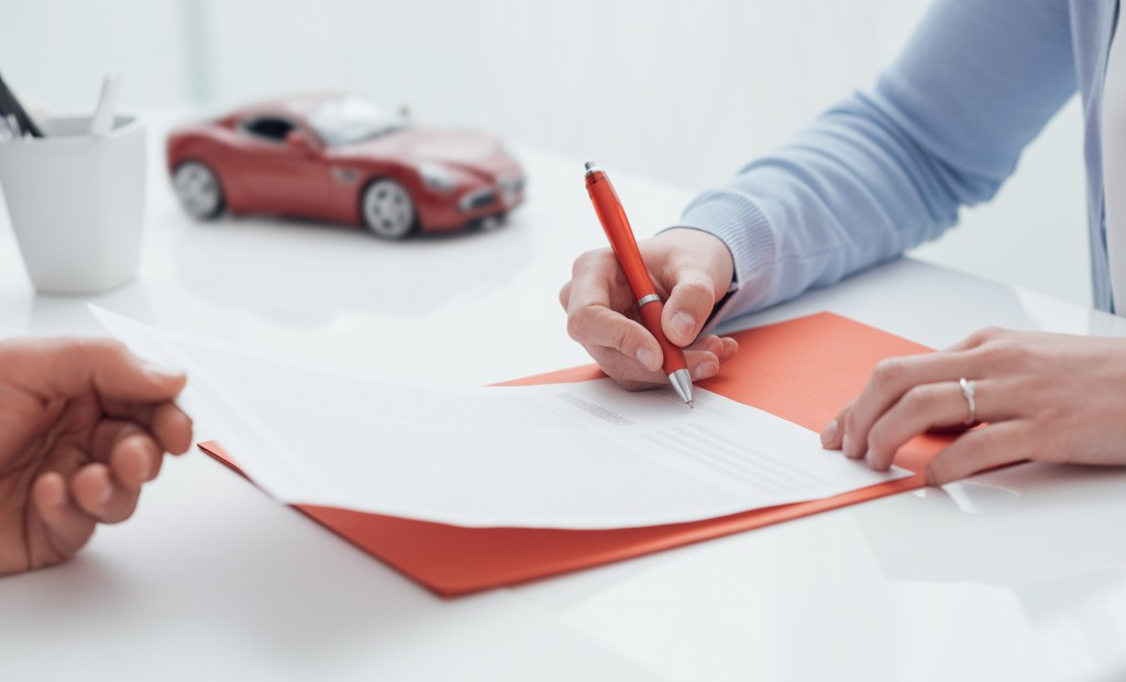 man signing a loan, a miniature red car on the background