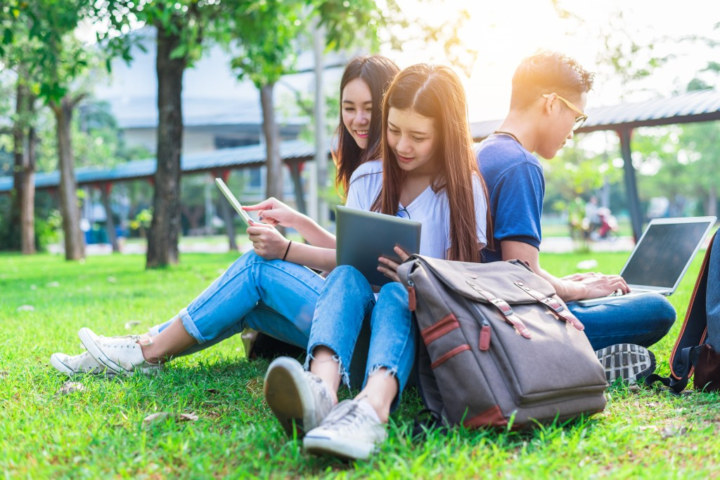 College students seated on grass using their tablets and laptop