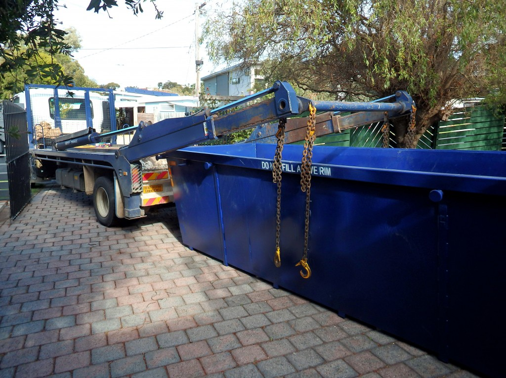 blue roll-off dumpster truck parked in front of gate