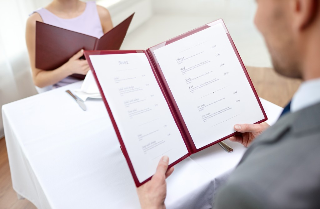 close up of couple with menu choosing dishes at restaurant