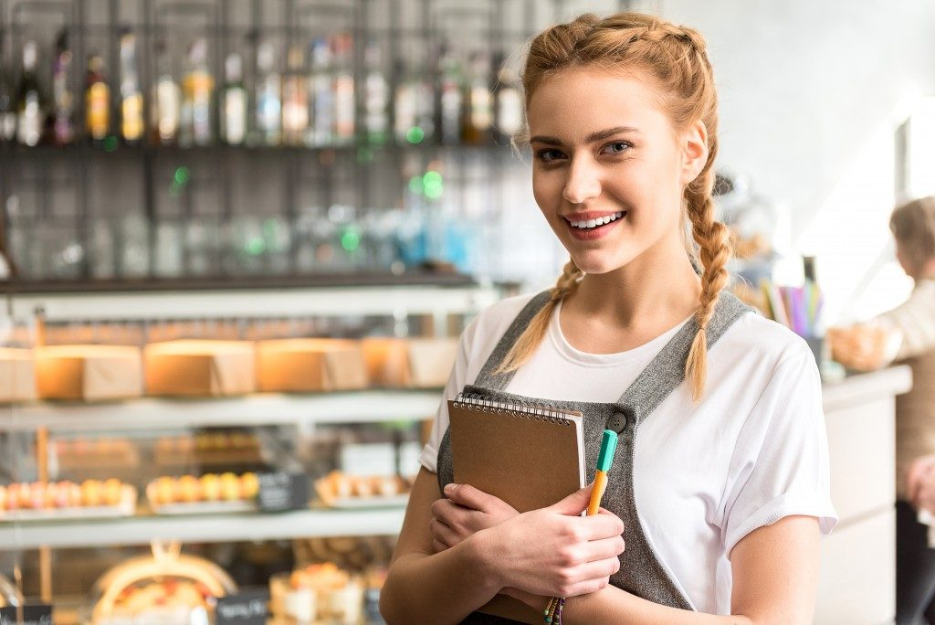 woman wearing a grey apron inside her bakery shop