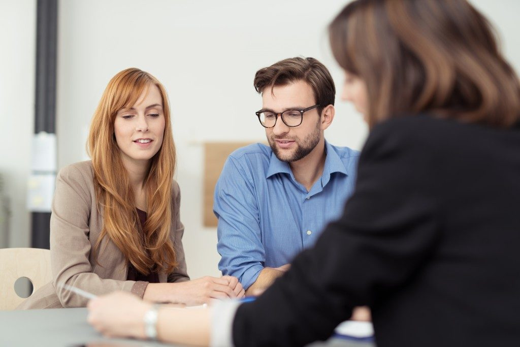 Couple discussing with an agent