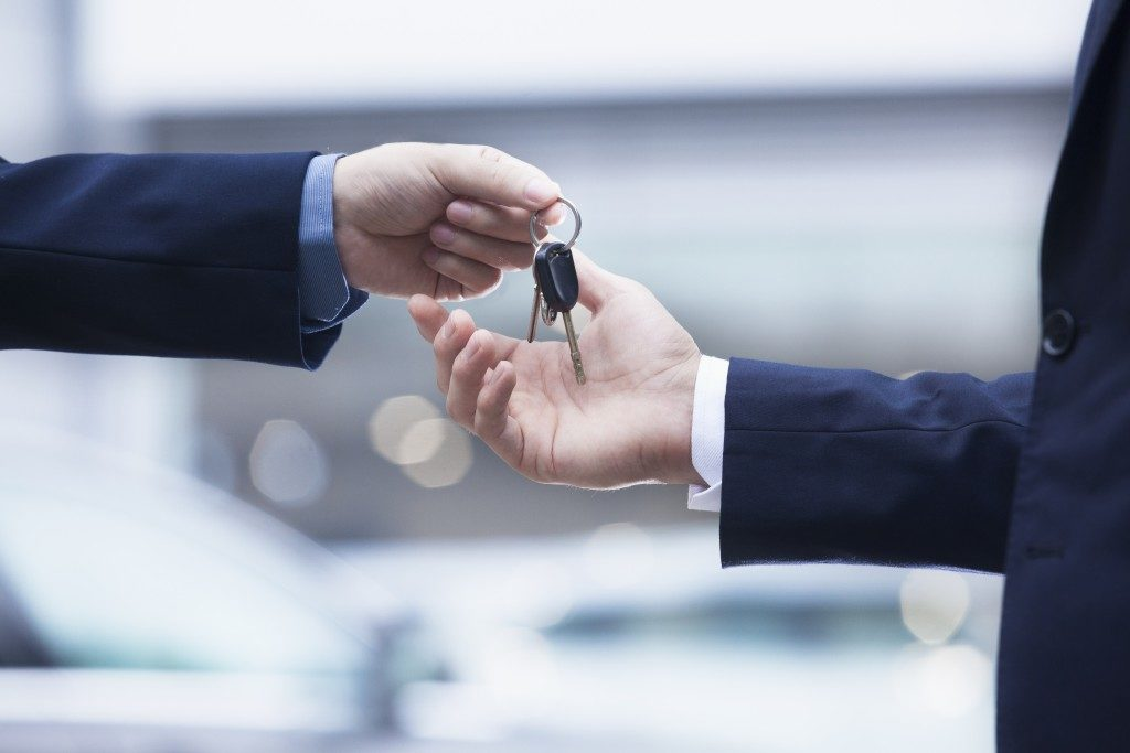 car dealer handing car keys to buyer