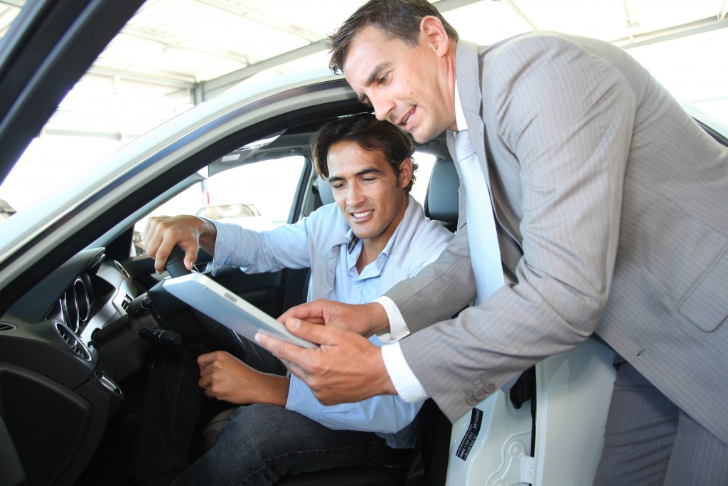 Car dealer with car buyer looking at tablet